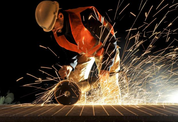 A man cuts the steel flooring before it is assembled on the bridge that crosses the Mriehel bypass on April 26. Photo: Chris Sant Fournier