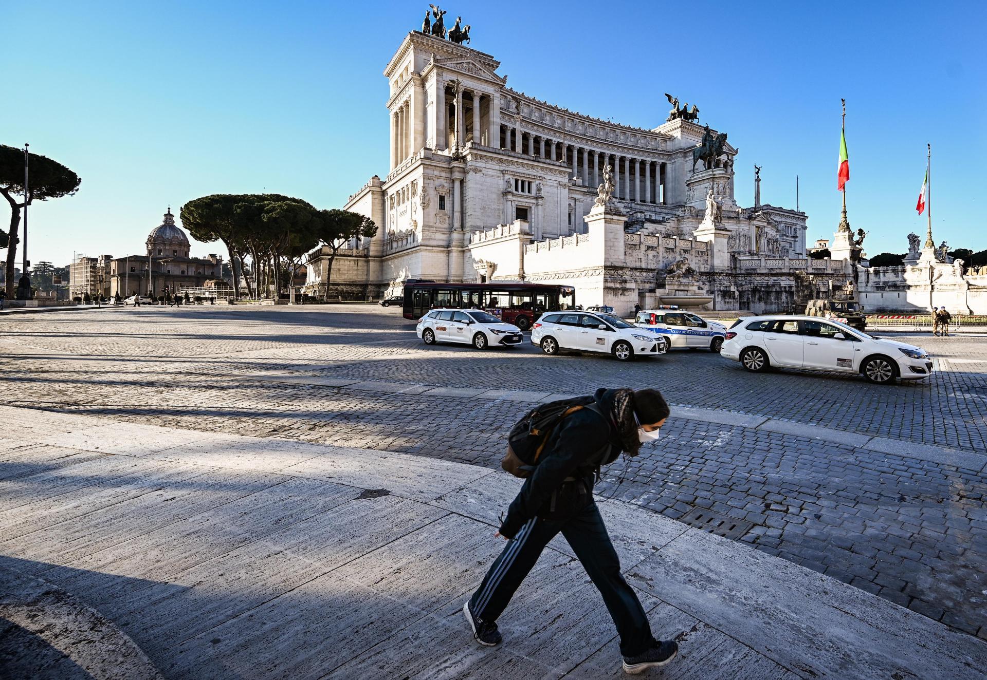 A woman wearing a respiratory mask walks past the Altare della Patria - Vittorio Emanuele II monument on Piazza Venezia in downtown Rome.