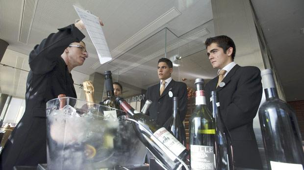 A sommelier explaining tostudents howto serve wine.