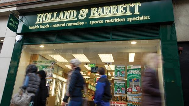 People passing by a Holland & Barrett store in England.