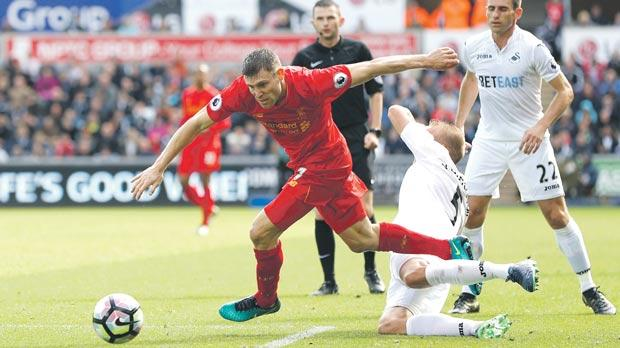 Liverpool's James Milner (left) forces his way past Swansea's Mike van der Hoorn during Saturday's game.