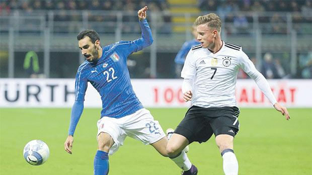 Italy's Davide Zappacosta (left) battles for the ball with Yannick Gerhardt, of Germany, in a friendly.