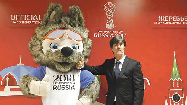 Germany coach Joachim Loew poses with the mascot of the 2018 Confederations Cup.