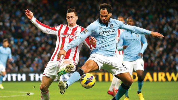 Manchester City's Joleon Lescott (right) defends possession from Geoff Cameron, of Stoke City.