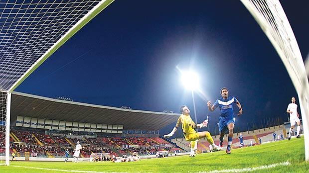 The ball flies into the net as Mosta striker Obinna Obiefule beats Valletta keeper Manuel Bartolo, yesterday. Photo: Paul Zammit Cutajar