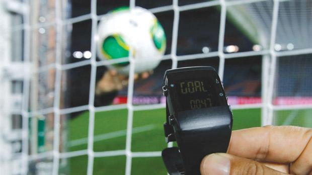 A FIFA official holds a watch used in a goal-line technology system by the FIFA-selected provider GoalRef, which is being used at the Club World Cup in Japan.