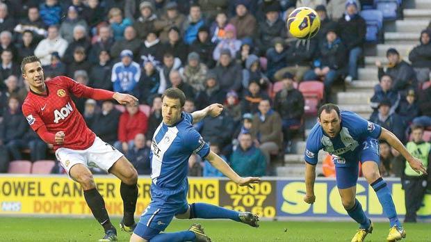 Manchester United striker Robin van Persie (left) scores against Wigan Athletic, yesterday.