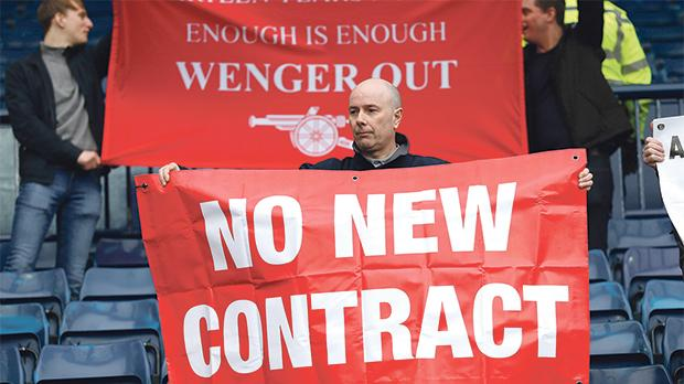 Arsenal supporters hold up banners directed at manager Arsene Wenger at the end of yesterday's match.