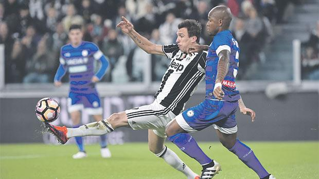 Juve striker Mario Mandzukic reaches the ball ahead of Udinese's Samir in Saturday's Serie A game.