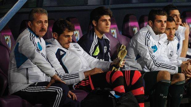 Goalkeeper Iker Casillas (second left) sits on the substitutes bench against Malaga.