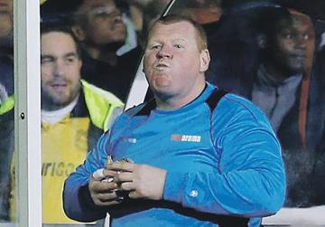 Wayne Shaw eating a meat pie during the match against Arsenal.