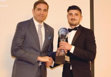 Xewkija goalkeeper Steve Sultana receives the player of the year award from GFA president Samuel Azzopardi.