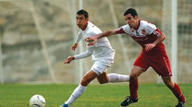 Valletta midfielder William Barbosa forces his way past Andrew Caruana Scicluna, of Melita, during Sunday's match at the Hibs Stadium. Photo: Darrin Zammit Lupi