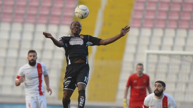 Qormi striker Alfred Effiong goes high for the ball against Valletta. Photo:Matthew Mirabelli