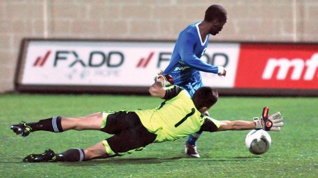 Mosta winger Ousseni Zongo tries to go past Ħamrun goalkeeper Andrea Cassar. Photo: Chris Sant Fournier