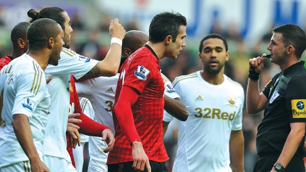 Robin Van Persie (centre) talks to the referee after being hit by Ashley Williams, of Swansea.