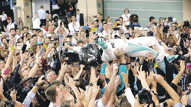 Crowd puller... Mercedes driver Nico Rosberg is carried by fans after winning the Formula One title in Abu Dhabi on Sunday.