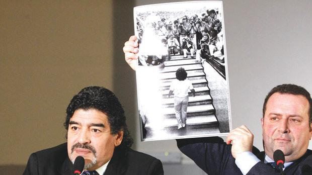 Diego Maradona (left) looks on as his lawyer Angelo Pisani holds a picture during a news conference in Naples yesterday.