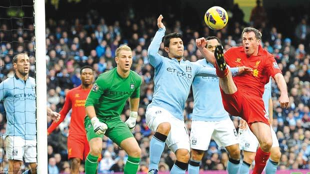 Man. City's Sergio Aguero (centre) is beaten to the ball by Jamie Carragher.