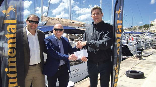 Malta Cruising Club commodore Wilfred Sultana (centre) receives the sponsorship from Massimo Povellato, of Continental Tyres, in the presence of Johann J. Cuschieri.