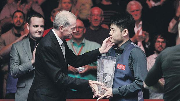 Liang Wenbo receives the English Open trophy from snooker legend Steve Davis on Sunday night.