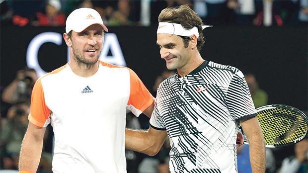Roger Federer (right) walks off the court with Mischa Zverev.