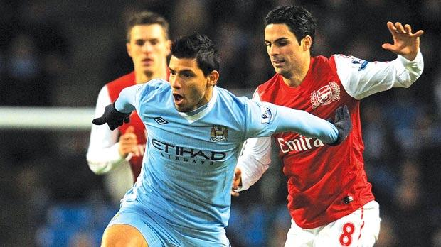 Man. City's Sergio Aguero runs past Arsenal's Mikel Arteta.