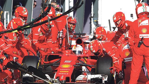 Sebastian Vettel has a tyre change at the Ferrari pit-lane during the Australian Grand Prix in Melbourne.