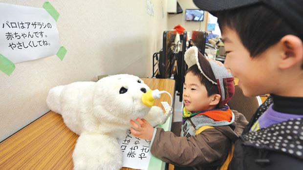 Children displaced by last year's tsunami playing with a therapeutic robot baby seal called Paro at temporary housing in Kesennuma, Miyagi prefecture.