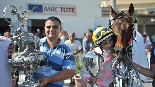 Giovanni Formica (right) and owner Jonathan Abela hold the trophies after Gold as Good won the Mediterranean Derby at the Marsa racetrack yesterday. Photo: Jason Borg