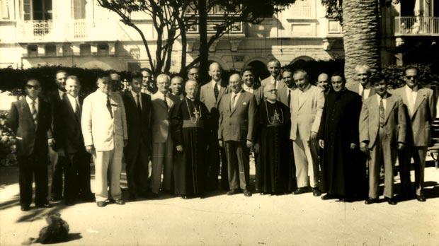 The inauguration of the Gozo Civic Council. Sir Guy Grantham, Governor of Malta (centre), with Anton Tabone, president of the Gozo Civic Council on his right, and (from left Amabile Grech (Kerċem), Anthony Cassar (Żebbuġ), Joseph Grech (Għasri), Carmelo Refalo (Xagħra), D.S. Stephens, assistant to the chief secretary, Joseph Buttigieg (Sannat), Salvatore Portelli (Għarb), Edgar Cassar, Commissioner for Gozo, Joseph Cauchi (Għajnsielem), Archbishop Michael Gonzi, Rev. Edward Bondì, Bishop's secretary, Anton Tabone (Victoria), Anton Vassallo (Fontana), Bishop Joseph Pace, Sir Archibald Campbell, chief secretary, Joseph Said (Nadur), Joseph Vella-Muskat (co-opted), Henry Borg-Cardona, secretary/treasurer of the council, Rev. Joseph Debrincat (Munxar), Anton Buttigieg (Qala), Laurence Apap (San Lawrenz), and Joseph Vella (Xewkija). Photo: Victor Vella-Muscat collection/National Archives Gozo