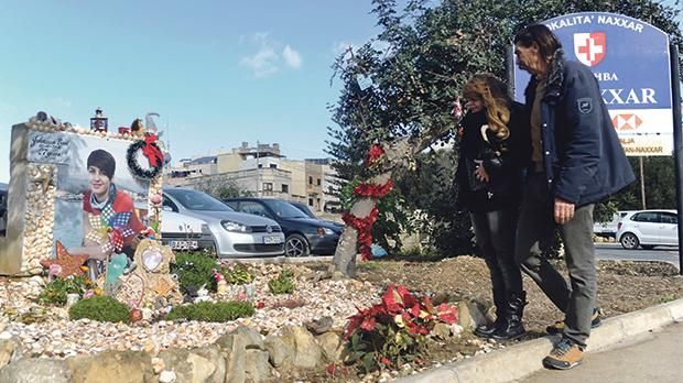 Josephine and Giuseppe Boni at their daughter's roadside memorial in Naxxar yesterday, metres away from where she was killed by a truck. Photo: Steve Zammit Lupi