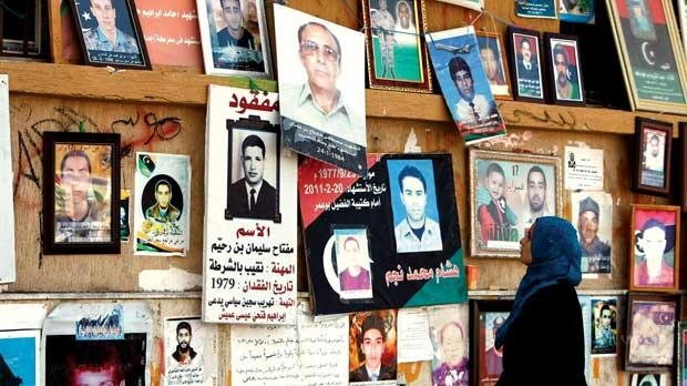 A woman looks at a wall in Tahrir Square with photos of victims of the Benghazi uprising yesterday. Photo: Darrin Zammit Lupi