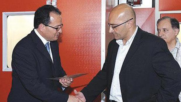 Former Parliamentary Secretary Chris Said presenting a certificate to then John's Garage CEO George Farrugia in 2010.