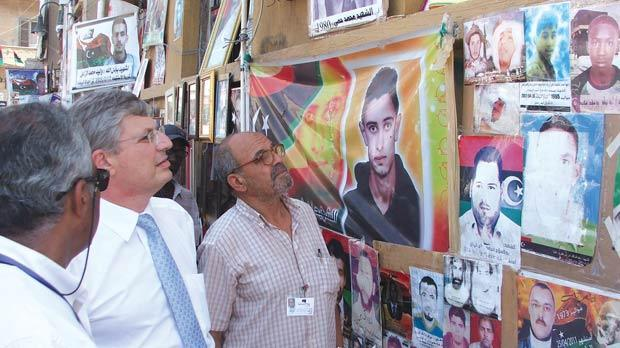 Tonio Borg viewing pictures of slain rebel fighters during his visit to Benghazi last month.