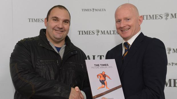 Allied Newspapers Group managing director Adrian Hillman presenting Daniel Caruana with a copy of The Times Picture Annual, which features his run on the cover. Photo: Matthew Mirabelli