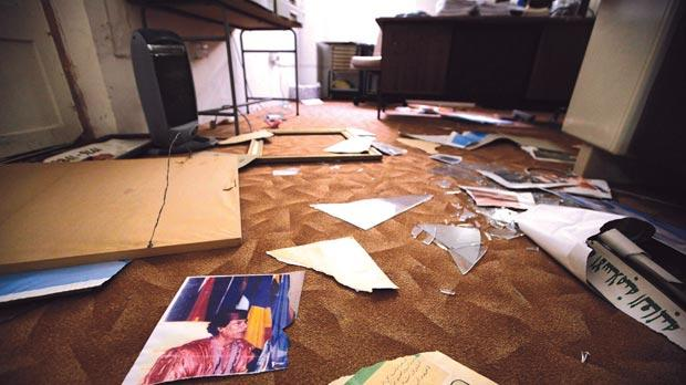 A torn picture of Muammar Gaddafi lies amid shattered glass and posters related to the colonel's philosophy after a group invaded the Libyan school at Ta' Giorni, yesterday. Photos: Darrin Zammit Lupi