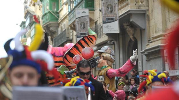 Inclement weather did not keep the carnival crowds away from the capital yesterday morning as a band and grotesque masks parade marched through the streets of Valletta. Photo: Jason Borg