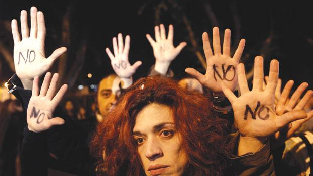 "Anti-bailout protesters raise their open palms showing the word ""No"" after Cyprus's parliament rejected a proposed levy on bank deposits in Nicosia last night. Photo: Reuters"