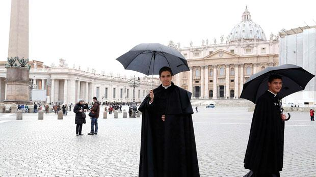 Two priests walk in St Peter's Square at the Vatican.