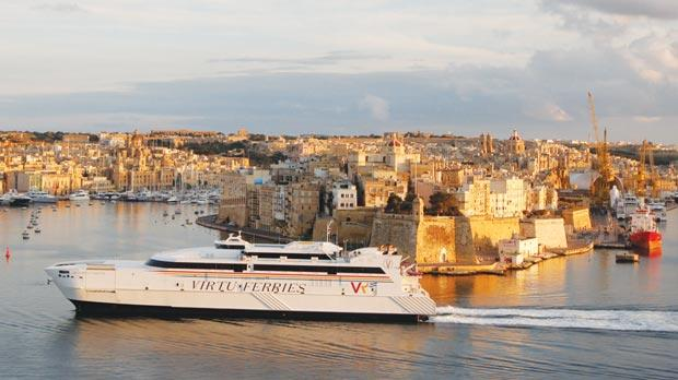 A Virtu Ferries catamaran sailing out of Grand Harbour in Valletta.