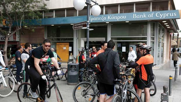 Cyclists outside a bank in Nicosia yesterday.