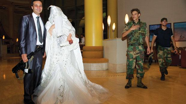 A newly-wed couple pose for photographs as the groom holds a machine gun in the lobby of a hotel in central Tripoli. Photo: Leon Neal/AFP