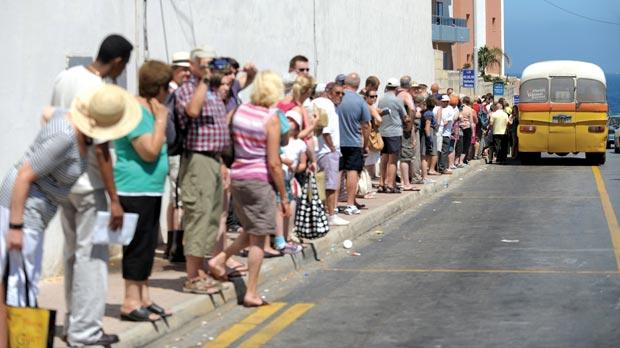 Tourists lined up for over an hour in Qawra to catch a bus to Valletta yesterday. Photo: Matthew Mirabelli