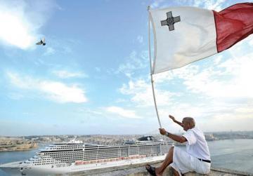 Charles Cremona waves the flag enthusiastically as the MSC Splendida leaves port. Photo: Jason Borg