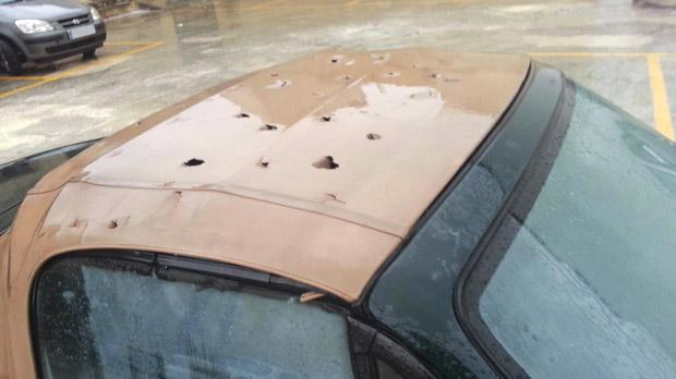 A convertible's canvas roof wrecked by precipitation.