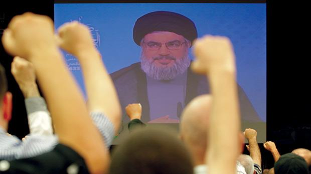 "Lebanese Shiite men raise their fists up as they listen to a speech via videolink by Hezbollah leader Hassan Nasrallah marking Al-Quds (Jerusalem) Day in the southern suburbs of Beirut last Friday. Nasrallah warned that his Lebanese Shiite militia would make the lives of Israelis ""a living hell"" if it is attacked. Photo: AFP"