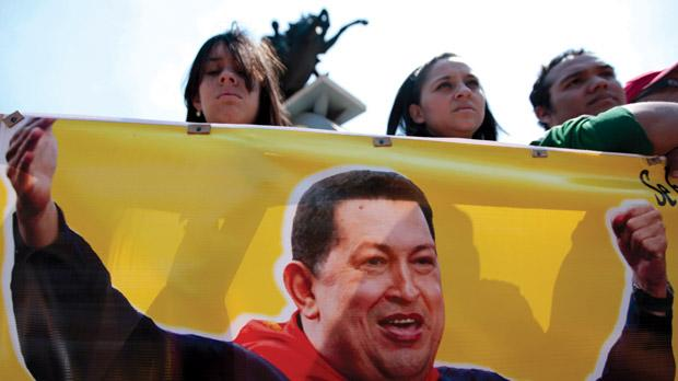 Supporters of Venezuela's late President Hugo Chávez hold a banner with an image of the leader during a tribute in Tegucigalpa last Thursday. Photo: Reuters