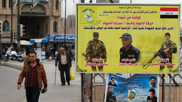 A man walks past a poster in Tahrir Square, Baghdad commemorating Shi'ite fighters killed in battles with Islamic State militants. Photo: Ahmed Saad/Reuters