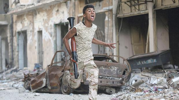 A member of the Libyan National Army runs during clashes with Islamist militants in Benghazi, Libya. Photo: Esam Omran Al-Fetori/Reuters